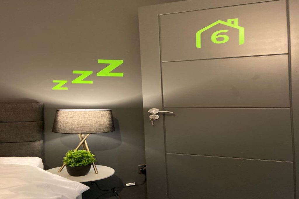 Traget Five completed renovation bedroom with a bright lamp next to bed, with grey wall and door and bright green neon signs