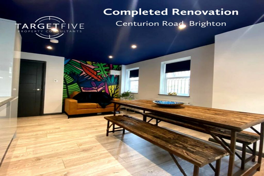 completed renovation living area, with blue ceiling, feature wallpaper, sofa and scaffold table