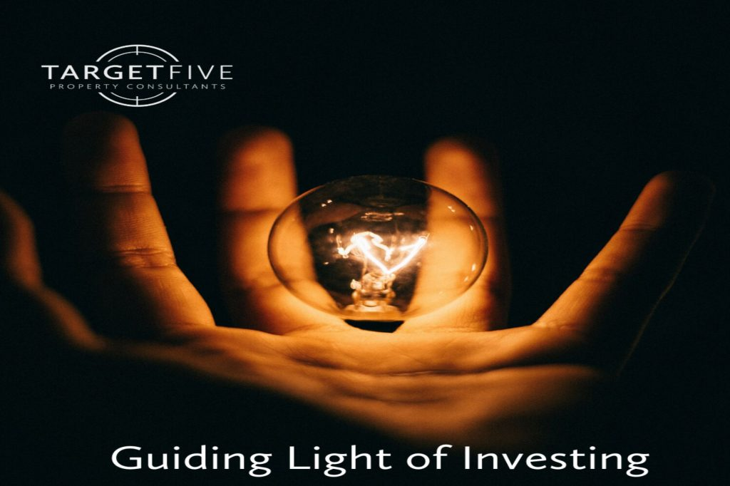 Hand holding an illuminated lightbulb with the Traget Five Property Consultant Logo in white in the top right and the title 'Guiding Light of Investing'